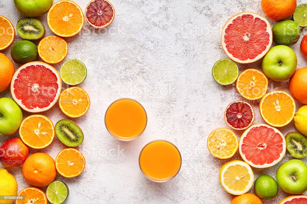 Fresh juice vitamin c drink in citrus fruits background flat lay, helthy vegetarian organic antioxidant detox stock photo