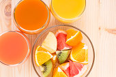 Fresh juices in three glasses with fruit salad. Vitamins background top view image