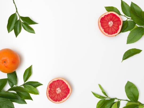 Frische, saftige Grapefruit mit grünen Zweigen liegen auf einem weißen Hintergrund – Foto