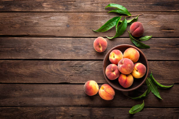 Fresh juicy peaches with leaves on dark wooden rustic background stock photo