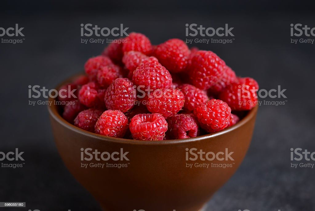 Fresh, juicy raspberries in a bowl on a black background royalty-free stock photo