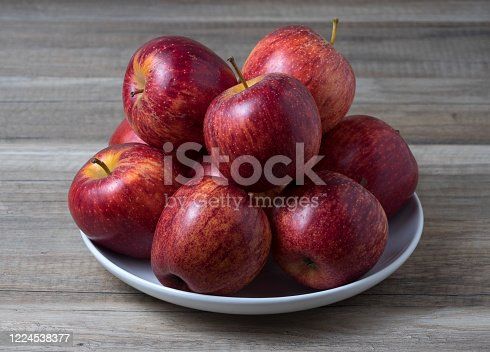 Fresh Juicy Ripe red apples in bowl on wooden white table.