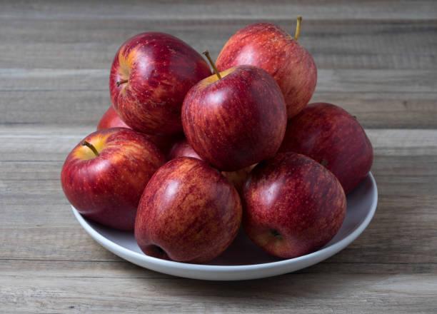 Frische Juicy Reife rote Äpfel in Schüssel auf weißem Holztisch. – Foto