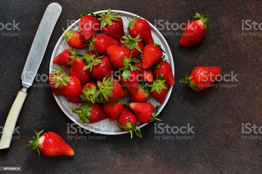 Fresh, juicy strawberries in a plate on a dark rustic background. Proper nutrition. Organic food. zbiór zdjęć royalty-free