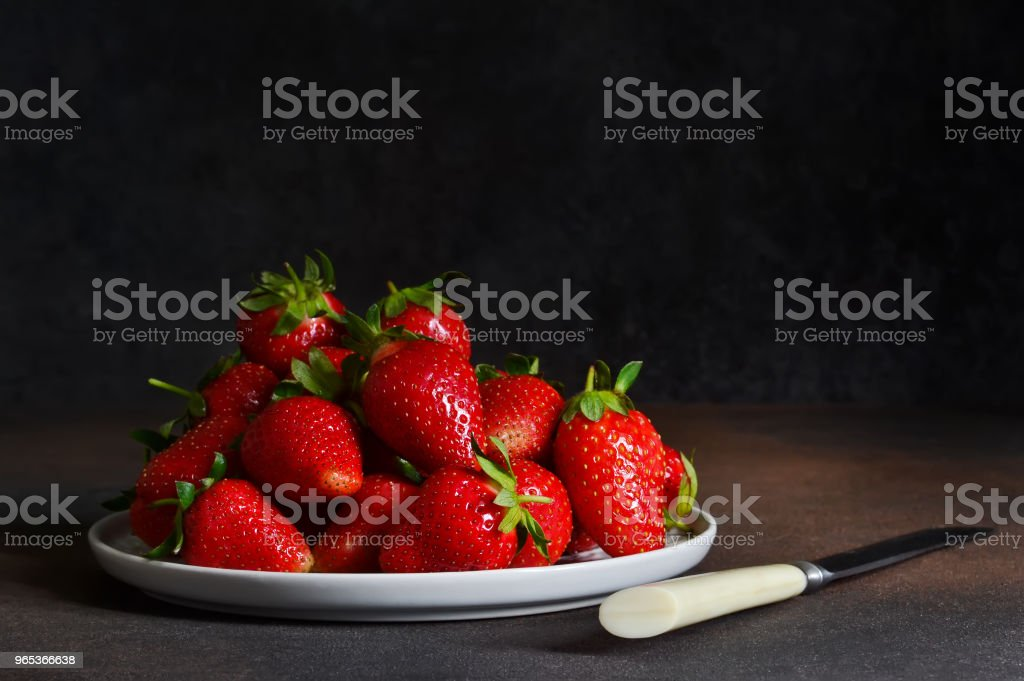 Fresh, juicy strawberries in a plate on a dark rustic background. Proper nutrition. Organic food. royalty-free stock photo