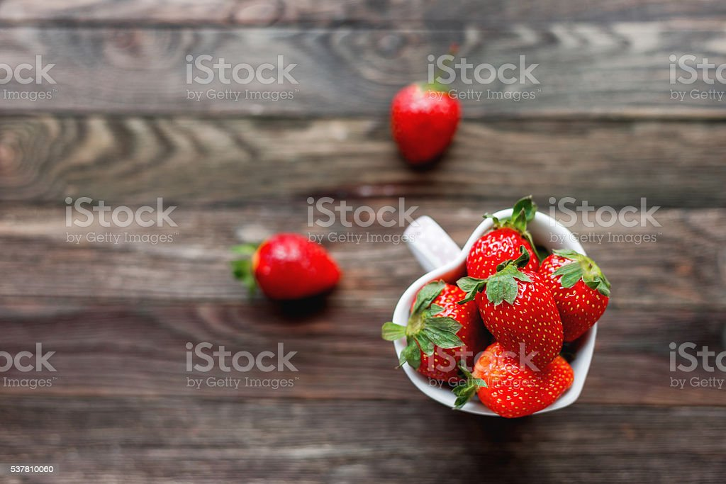 Fresh juicy strawberries in cup shaped as a heart stock photo