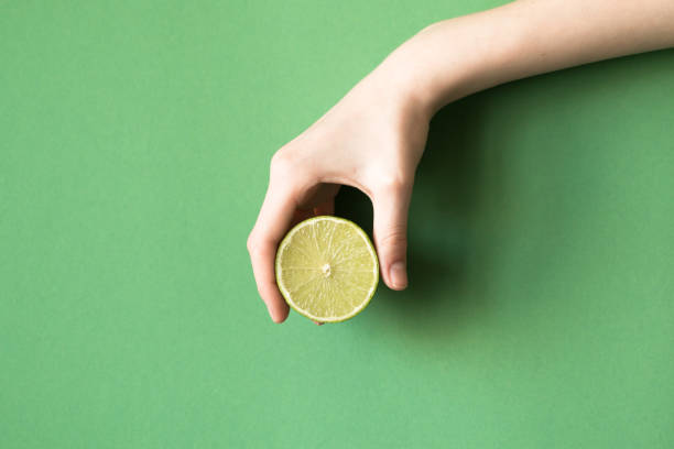 fresh juicy tasty green lime in a human hand on green background - squeezing stock pictures, royalty-free photos & images