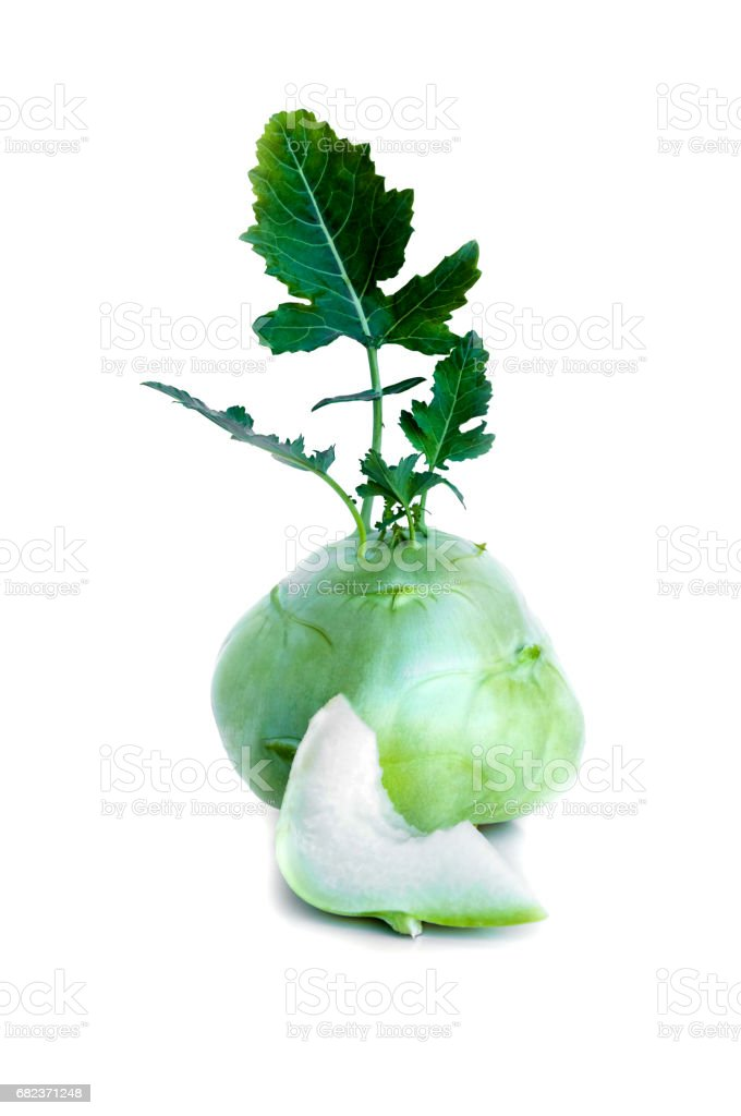 Fresh kohlrabi with a bited piece and green leaves on isolated white backround stock photo