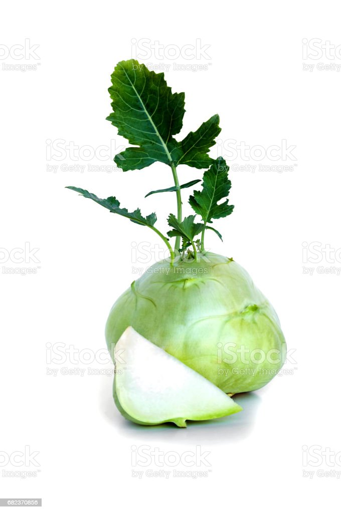 Fresh kohlrabi with a cuted piece and green leaves on isolated white backround stock photo