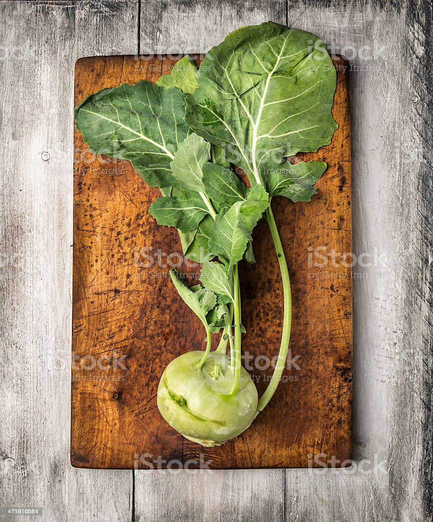 Fresh Kohlrabi with leaves on cutting board stock photo