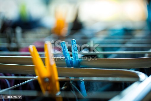 Close up color image depicting freshly laundered clothing drying on an airer in a domestic room at home. The clothes are attached to the airer by colorful plastic pegs.