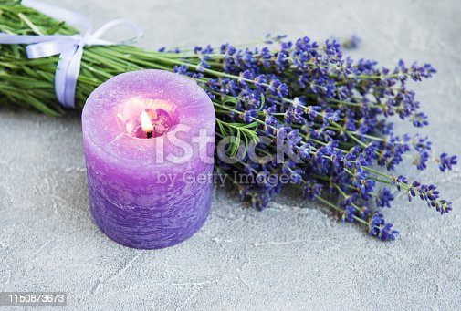 fresh lavender flowers and candle on a concrete background