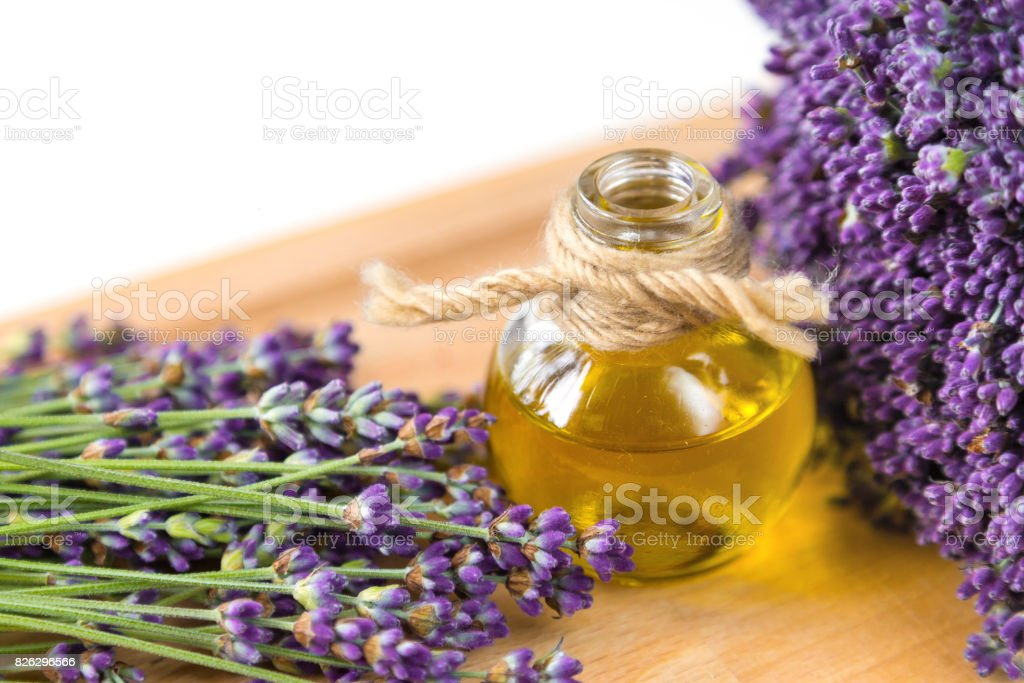 Fresh lavender flowers and oil on wooden background stock photo