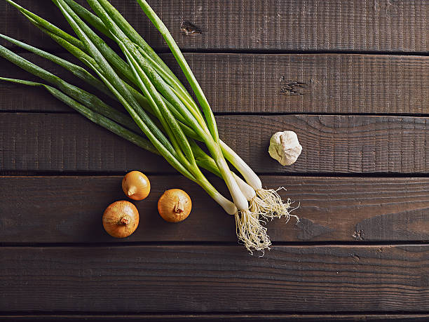 Fresh leek, onion and garlic on a wooden background. Fresh leek, onion and garlic on a wooden background. Top view. Free copy space. leek stock pictures, royalty-free photos & images