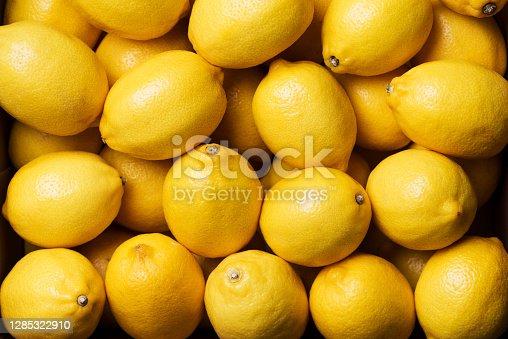 Fresh lemon background. Top view. Citrus fruits. Vitamins for health. Box of yellow lemons. Liposomal vitamin C.