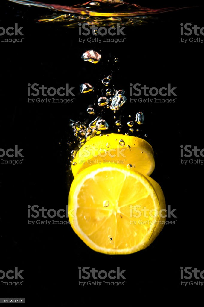 Fresh lemon dropped into water royalty-free stock photo