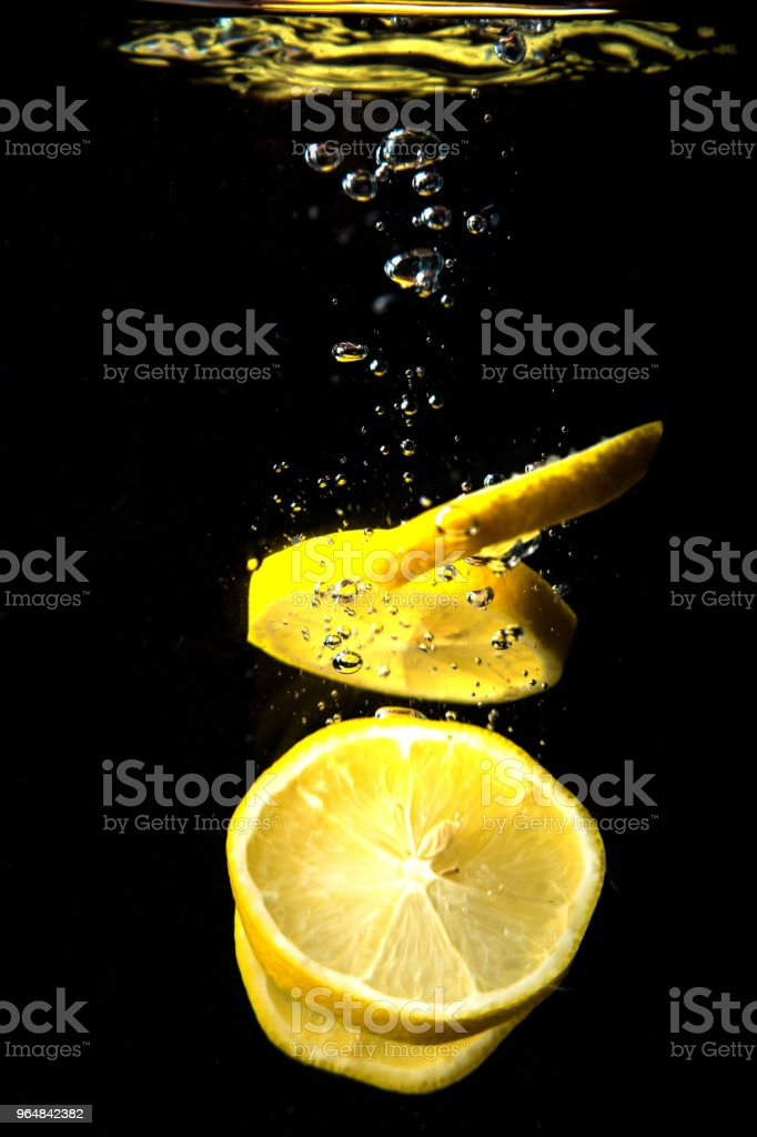 Fresh lemon dropped into water royalty-free stock photo