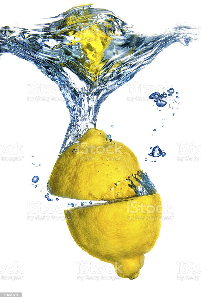 Fresh lemon dropped into water with bubbles isolated on white royalty-free stock photo