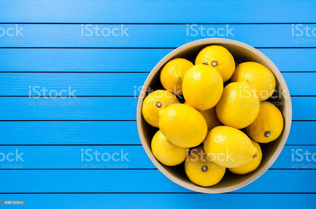 Fresh lemons in bowl on wooden table stock photo