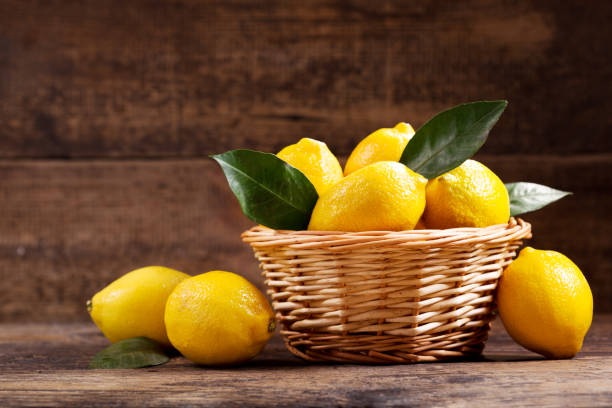 fresh lemons with leaves in a basket stock photo