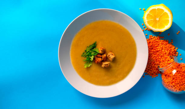 Fresh lentil cream soup in white plate on blue background, top view stock photo