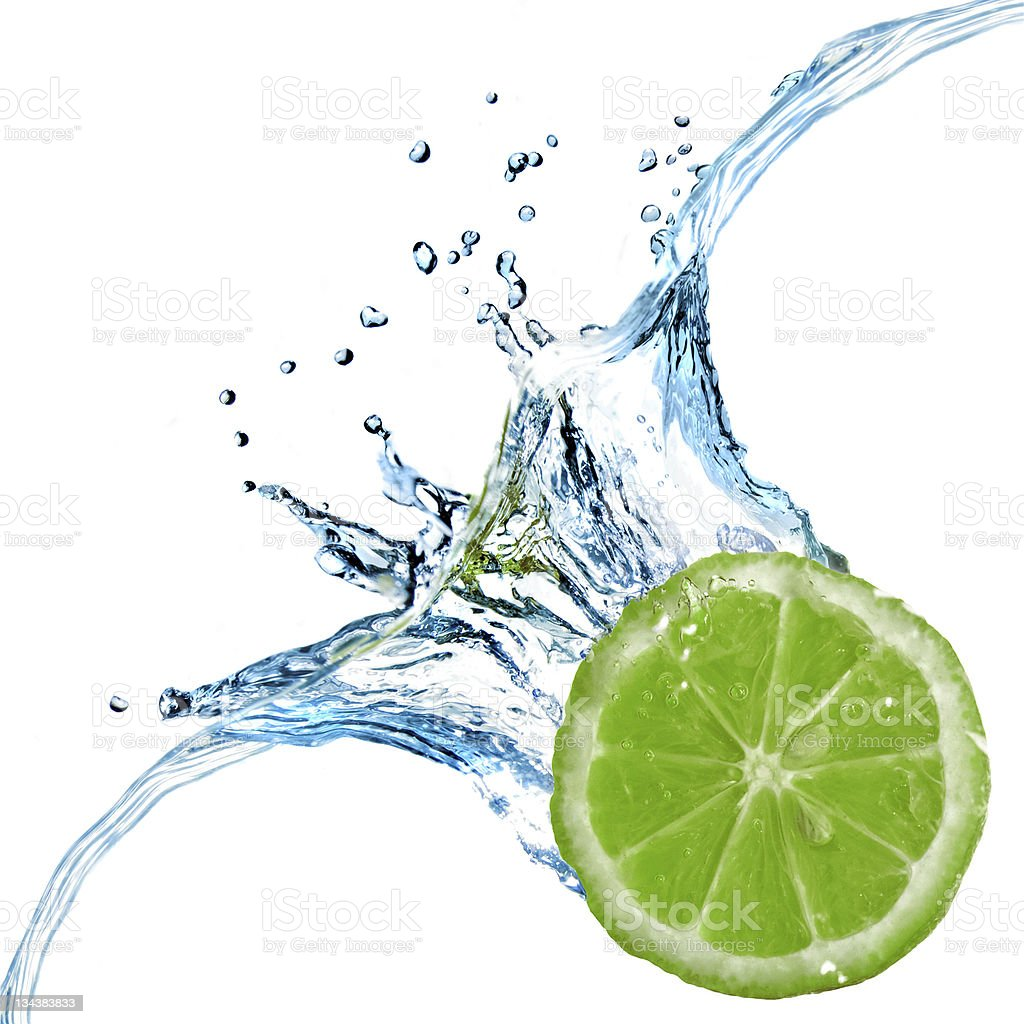 Fresh lime dropped into water with splash isolated on white stock photo