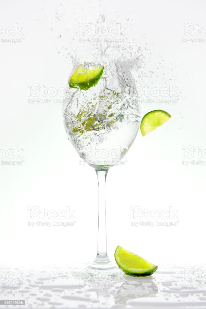 Fresh lime falling into a splashing sparkling water. stock photo