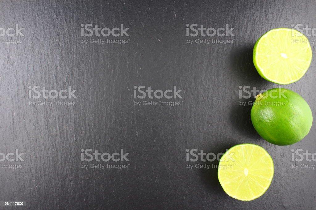 färsk lime frukt på en griffeltavla tallrik mat bakgrundsstruktur royaltyfri bildbanksbilder