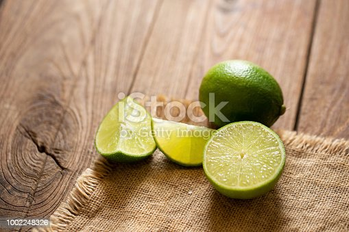 Fresh lime on the brown wooden table.