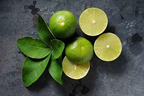 fresh limes on dark background stock photo