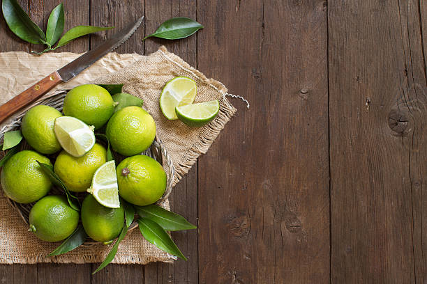 Fresh limes with knife and leaves Fresh limes with knife and leaves on a wooden  table lime stock pictures, royalty-free photos & images