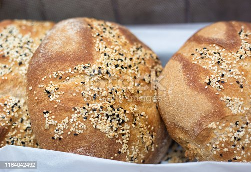 Fresh Loaves of Round Bread with Sesame Seeds in Bakery Window, Close-up. Shot in France.
