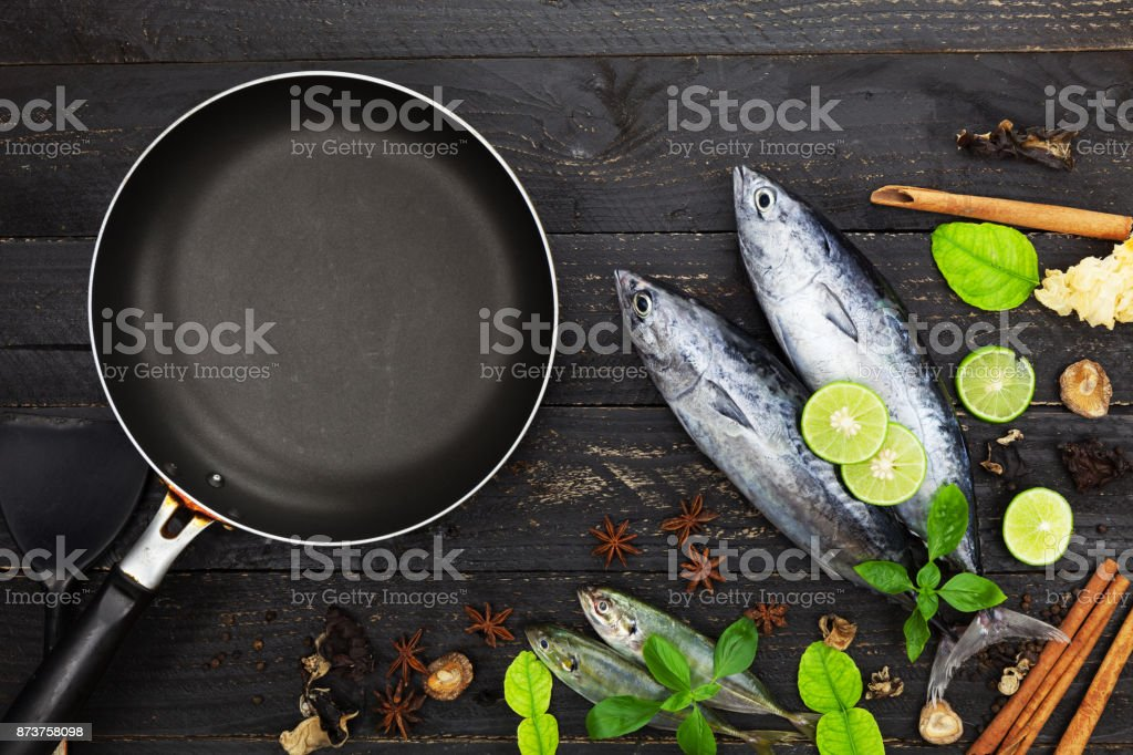 Fresh Lungtail Tuna fish and black frying pan on dark black background, Fish with spices and vegetables, cooking background concept. stock photo