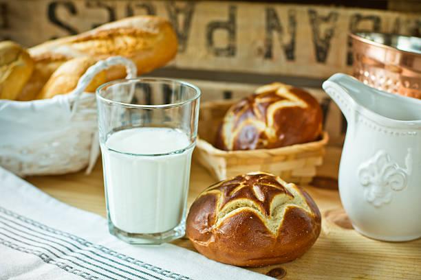 fresh lye rolls in wicker basket, a glass of milk - laugenstangen stock-fotos und bilder
