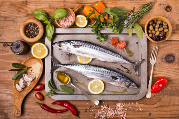 fresh mackerel fish ready to cook fresh sea fish in a pan ready to cook with ingredients on rustic wooden table rosmarino stock pictures, royalty-free photos & images