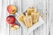 Fresh made Apple Popsicles (selective focus; close-up shot) on a vintage background