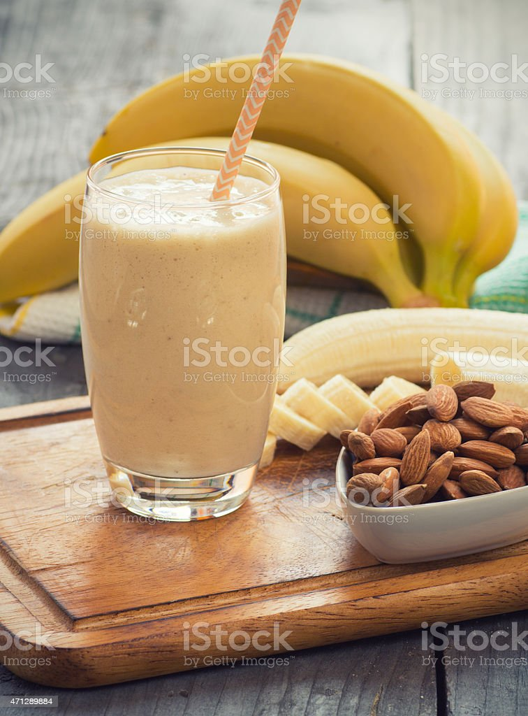 Fresh made Banana smoothie on wooden background stock photo