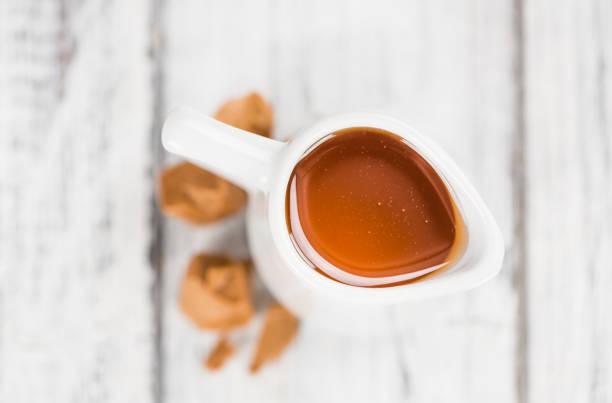 frisch gemachte karamell-sirup - karamellsirup stock-fotos und bilder