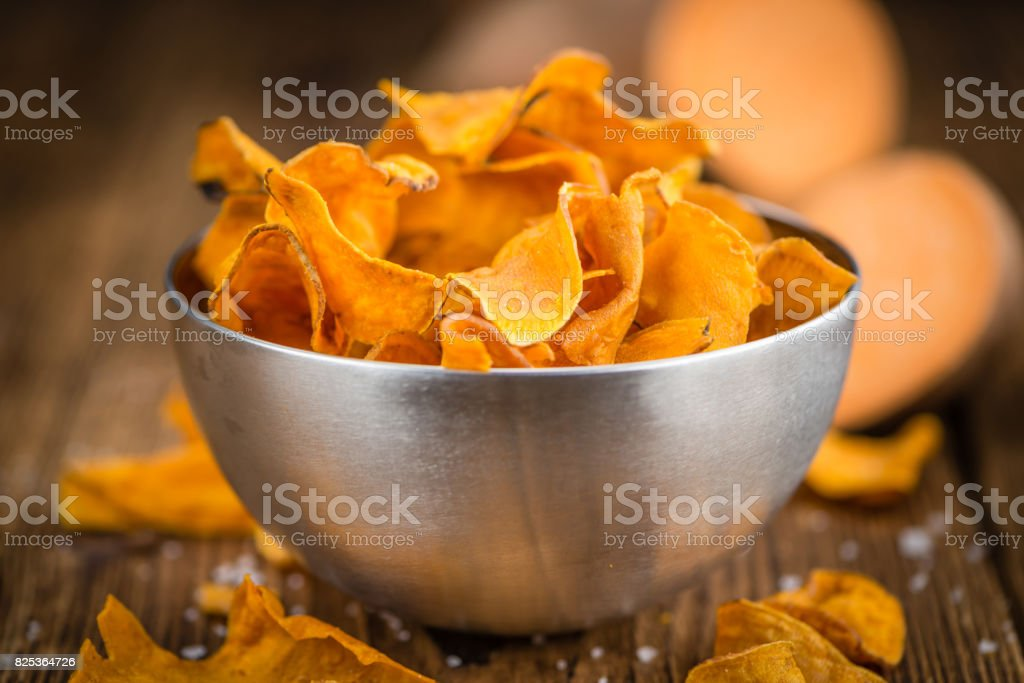 Fresh made Sweet Potato Chips on a rustic background stock photo