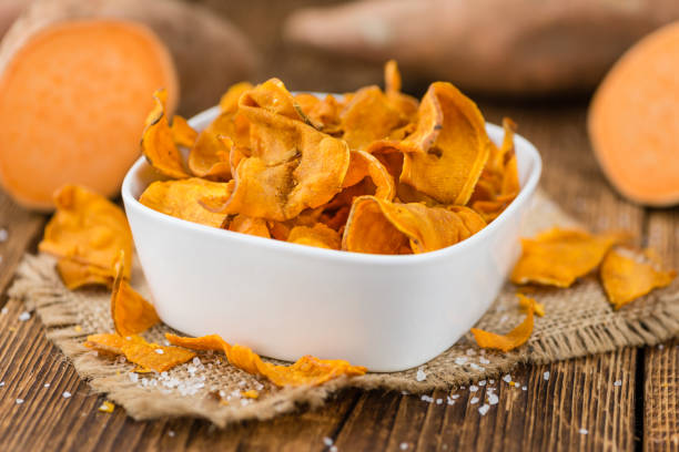 Fresh made Sweet Potato Chips Sweet Potato Chips on a vintage background as detailed close-up shot, selective focus sweet potato stock pictures, royalty-free photos & images