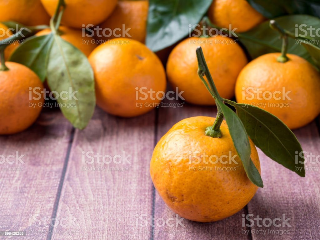 Fresh Mandarin or tangerine with stems and leaves on a brown wooden background copy space stock photo