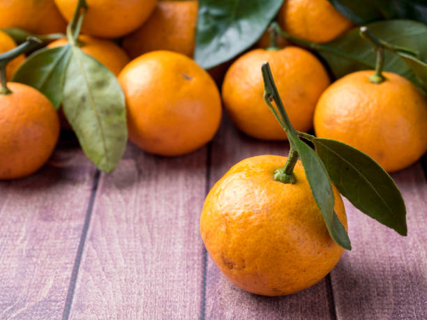 fresh mandarin or tangerine with stems and leaves on a brown wooden background copy space - imperfection stock photos and pictures