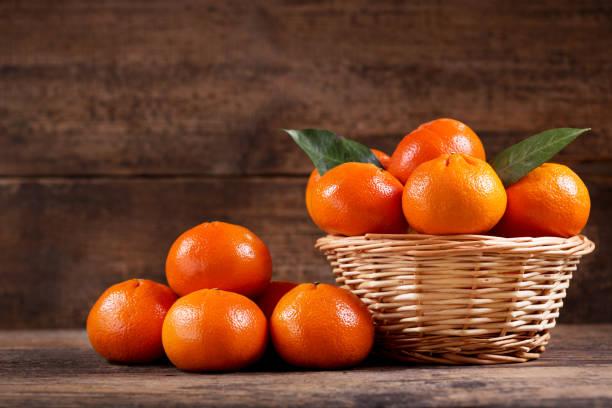 fresh mandarin oranges fruit  in a wooden basket close up of fresh mandarin oranges fruit  in a wooden basket tangerine stock pictures, royalty-free photos & images