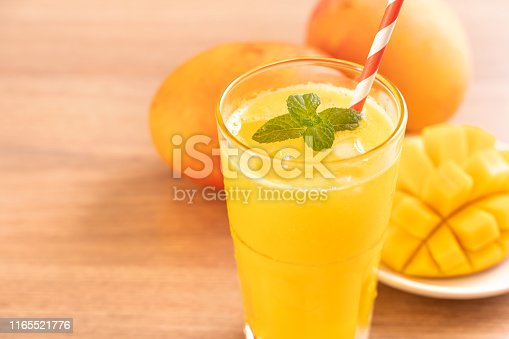 Fresh mango juice with beautiful chopped pulp flesh and straw on bright wooden table background. Tropical fruit design concept. Close up, copy space.
