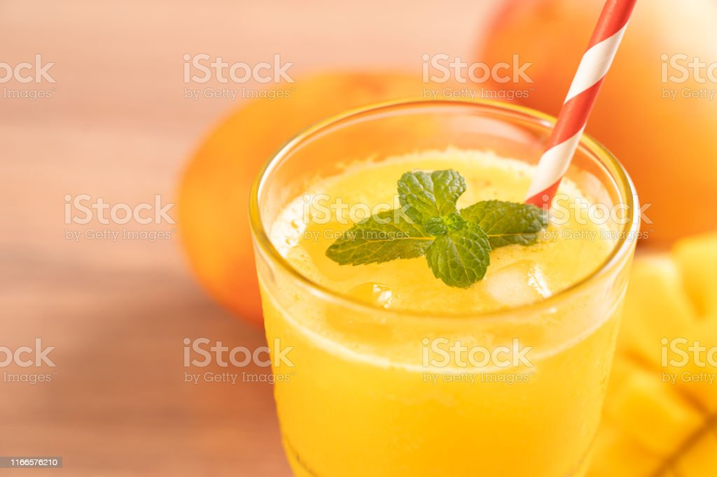 Fresh mango juice with beautiful chopped pulp flesh on bright wooden...