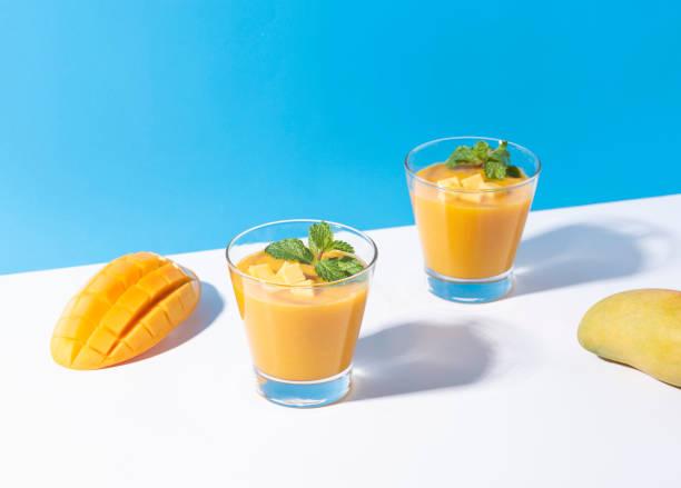 Frische Mango-Smoothie und reife Mango-Seise auf farbigem Hintergrund. Sommergetränk. – Foto