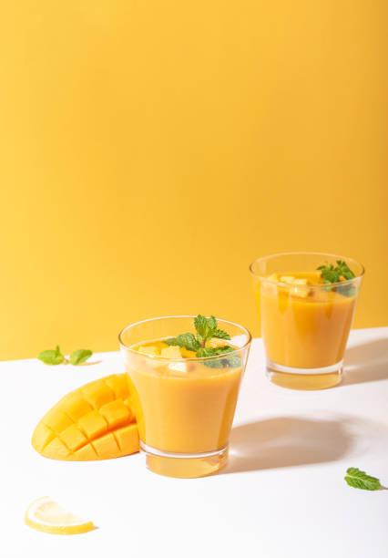 Frische Mango-Smoothie und reife Mango-Seise auf gelbem Hintergrund. Sommergetränk. – Foto