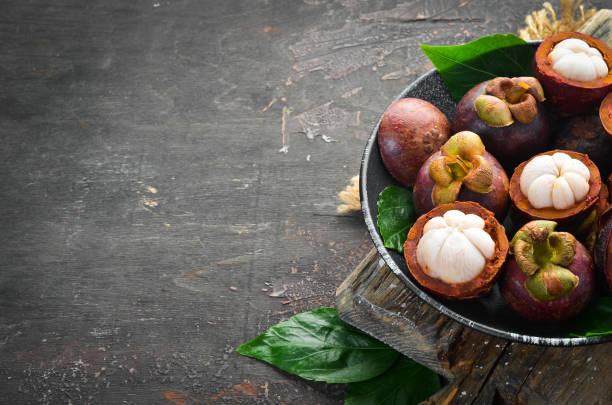 Mangostão fresco no prato. Frutas tropicais. Vista de cima. Espaço livre para o texto. - foto de acervo