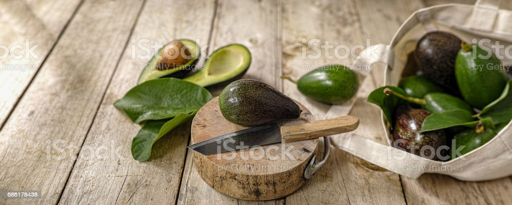 Fresh market avocado on a wooden cutting board next to a knife with more avocados in a cotton reusable shopping bag to the right of the image. stock photo