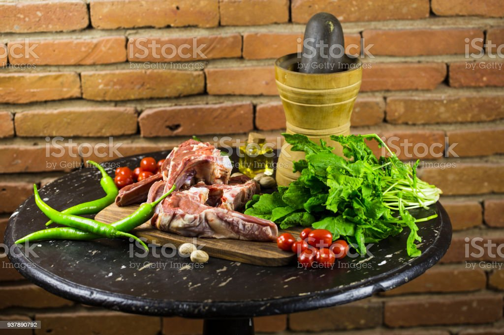 Fresh meat and vegetables on an old wooden table on the background of an old brick wall stock photo